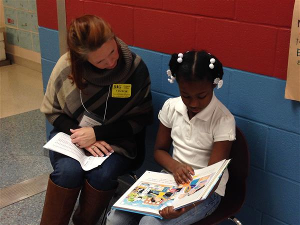 Volunteer reading with a student